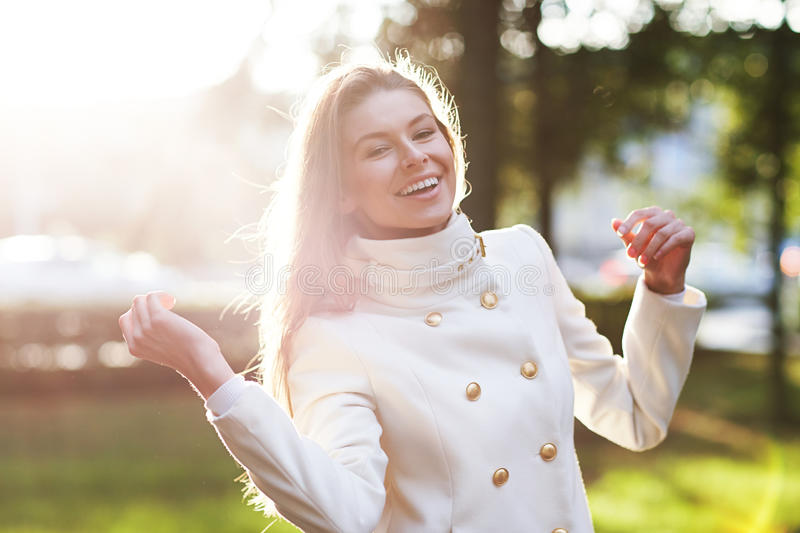 Young woman outdoors portrait. Soft sunny colors. Young woman in white coat outdoors portrait. Soft sunny colors royalty free stock photos