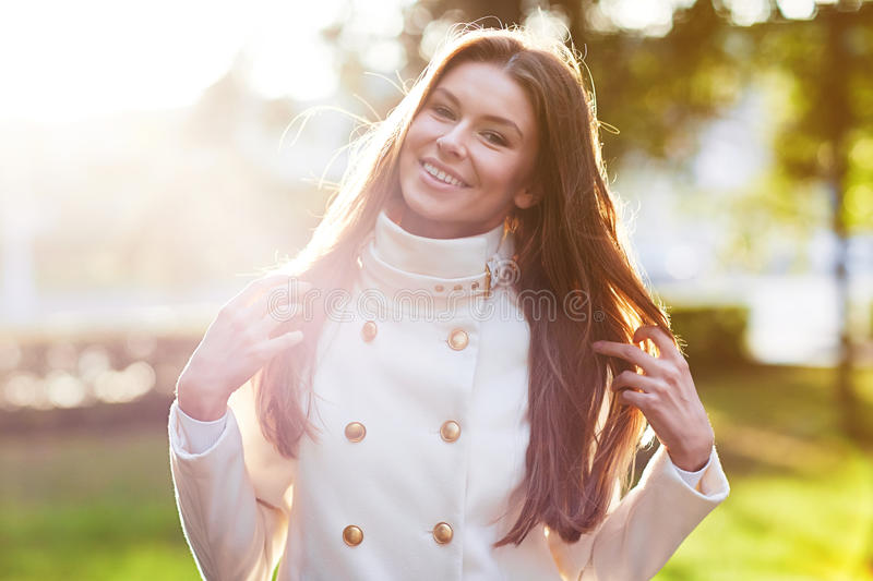 Young woman outdoors portrait. Soft sunny colors. Young woman in white coat outdoors portrait. Soft sunny colors stock images