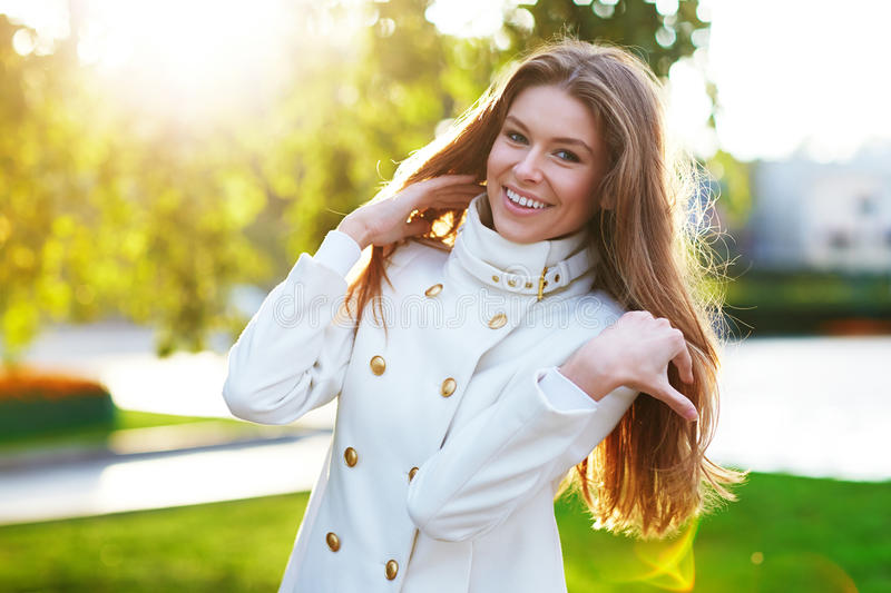Young woman outdoors portrait. Soft sunny colors. Young woman in white coat outdoors portrait. Soft sunny colors stock photo