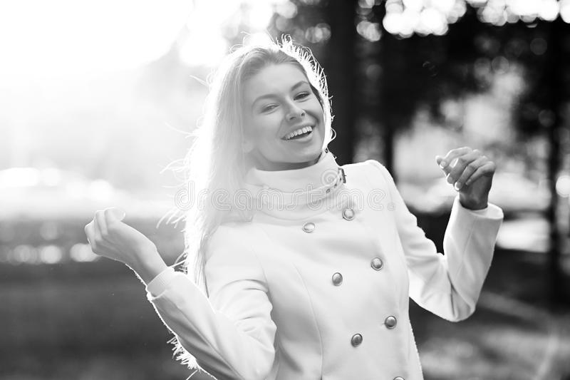 Young woman outdoors portrait. Soft sunny colors. Young woman in white coat outdoors portrait. Soft sunny colors. Black and white image stock image