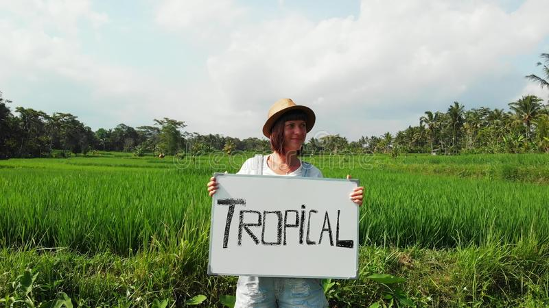 Young woman outdoors with whiteboard and handwriting word tropical on it. Drone flying footage. Green bright tropical stock photography