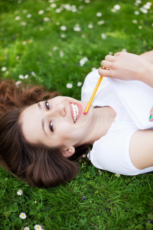 Download Young Woman Outdoors With Workbook And Pencil Stock Photo - Image: 25247284