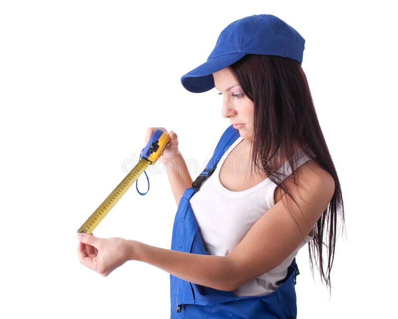 Young woman in overalls with a measuring tape royalty free stock photography