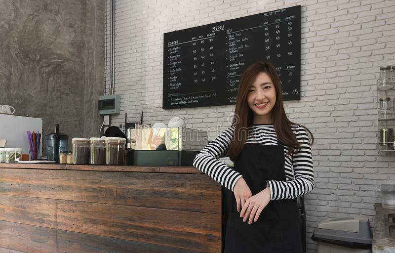 Young woman owner of a cafe stand in front of coffee counter, yo stock photos