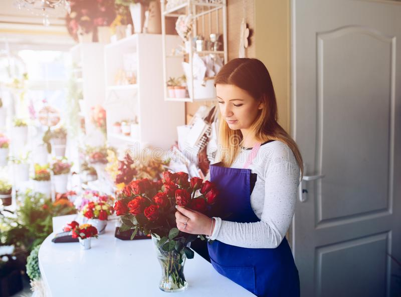 Young woman owner of florist shop preparing bouquet of red roses. royalty free stock images