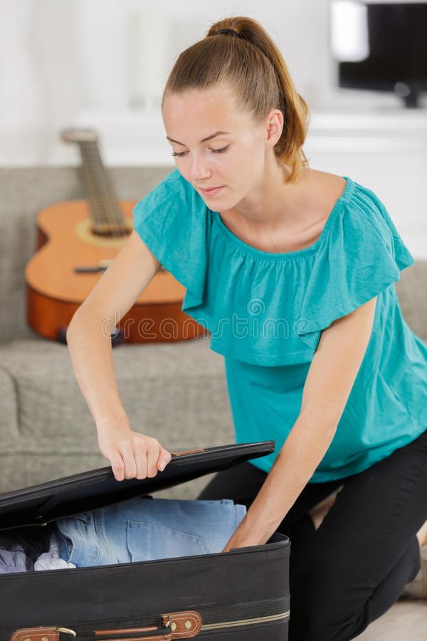 Young woman packign suitcase royalty free stock photography