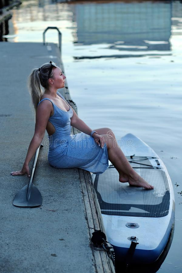 Young woman with paddle board and oar sitting on pier in Vancouver Yaletown. stock image