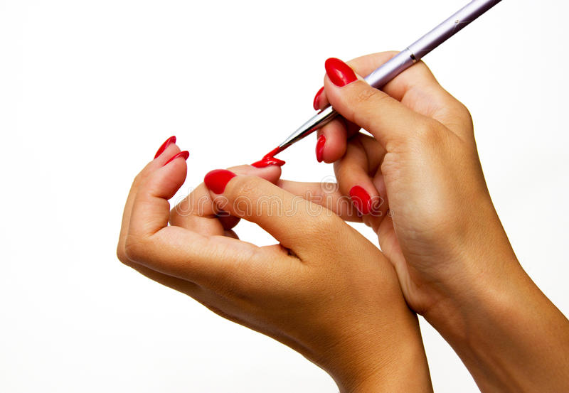 Young woman paint her nails royalty free stock photo