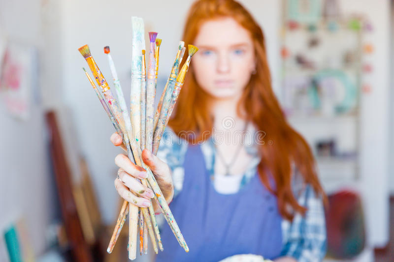 Young woman painter showing dirty paintbrushes in artist workshop. Young woman painter with long red hair in blue apron showing dirty paintbrushes in artist stock photo