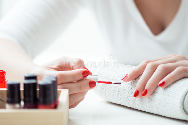 Young woman is painting her nails stock photography