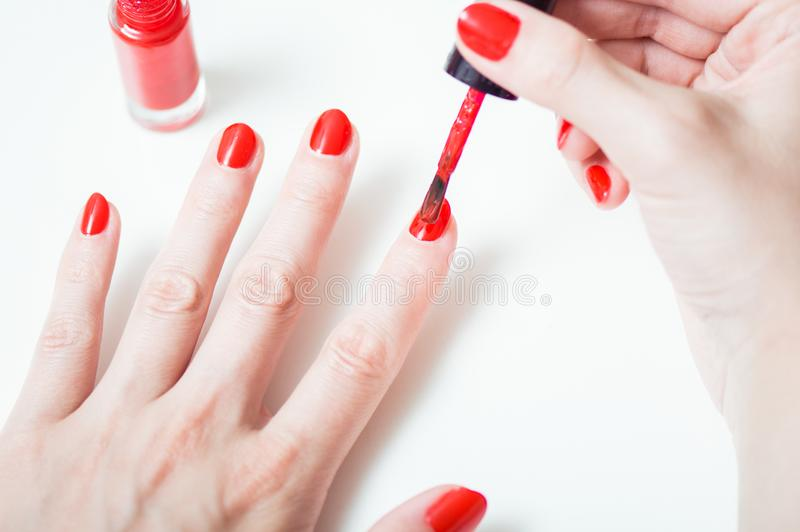 Young woman is painting her nails stock photos