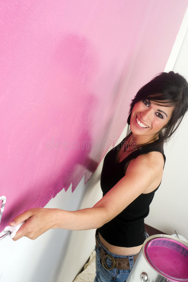 Young happily woman painting wall pink DIY project stock image