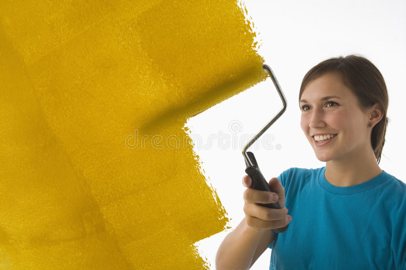 Young woman painting walls. Young woman painting the wall yellow with a roller royalty free stock photography