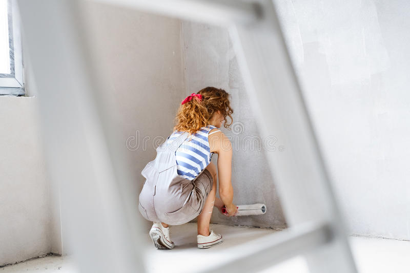 Young woman painting walls of her new house. stock images