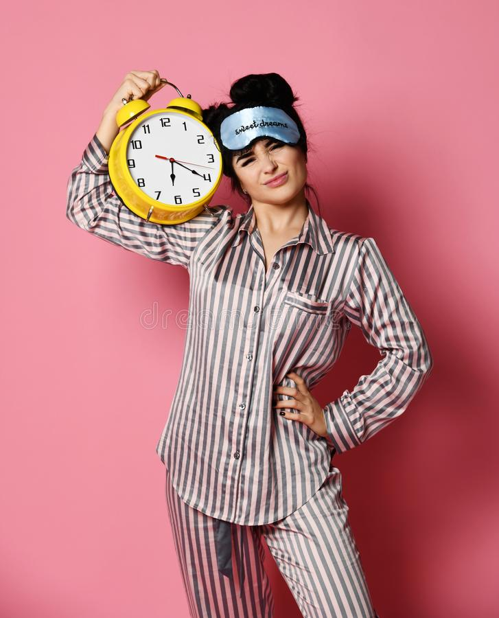 Young woman in pajama just after sleep woke up with sleepy bandage mask hold yellow alarm clock royalty free stock photography