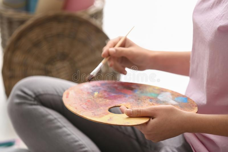 Young woman with palette and paintbrush, closeup stock image