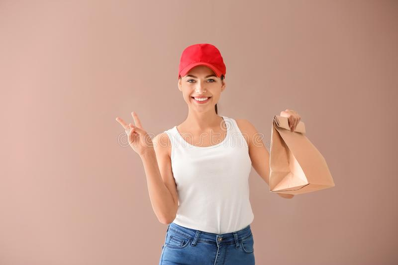 Young woman with paper bag showing victory sign on color background. Food delivery service royalty free stock photos