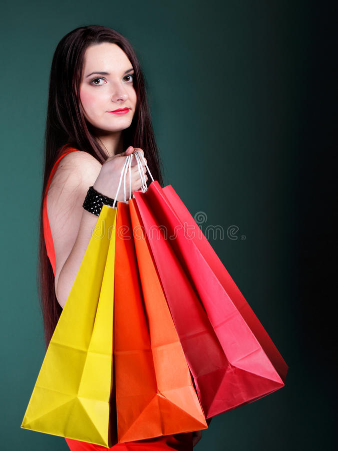 Young woman with paper multi coloured shopping bag. Young woman long hair with paper multi coloured shopping bags on green background. Sales and discounts royalty free stock images