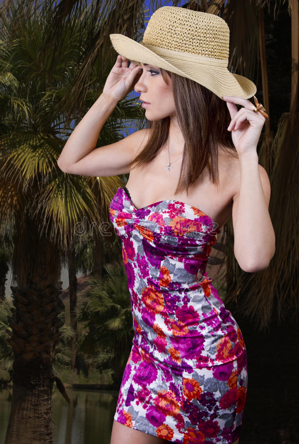 Young woman in paradise. Beautiful young petite brunette woman wearing a straw summer hat on an island paradise stock photo