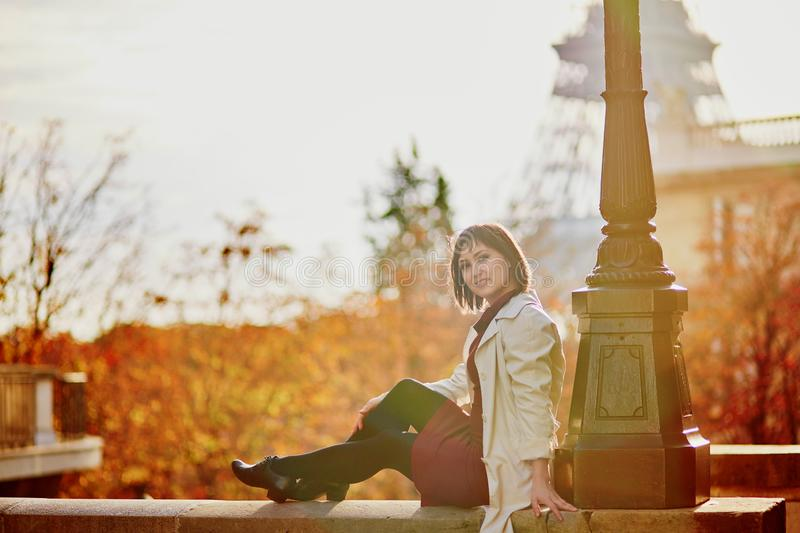 Young woman in Paris near the Eiffel tower on a fall day royalty free stock image