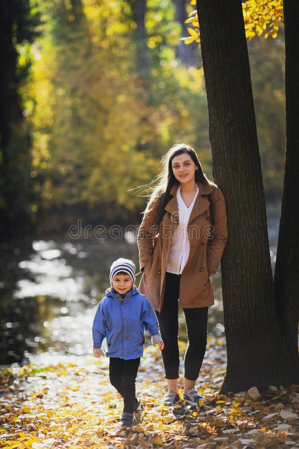 Young woman in the park in autumn with a child. mother with son. royalty free stock images