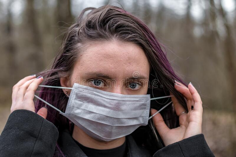 Young woman in park putting on a light, soft protective medical mask for face protection against virus outbreak, close up portrait stock photos