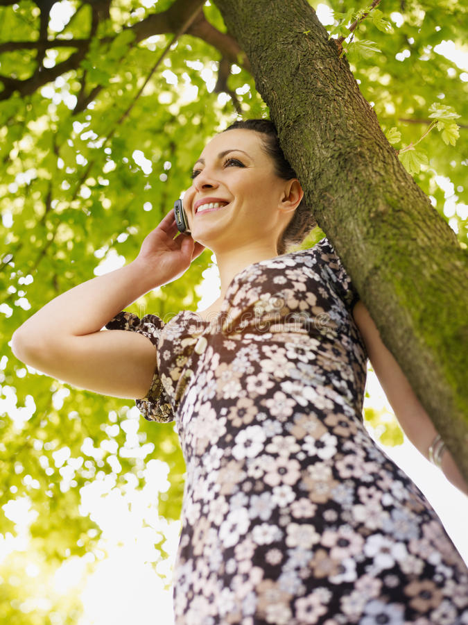 Young woman in park, smiling royalty free stock images