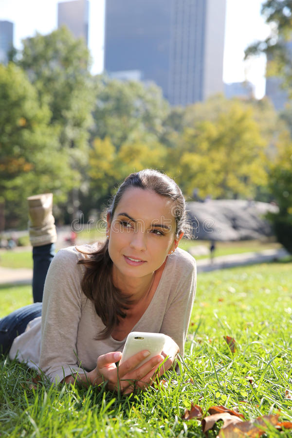 Young woman in park using smartphone stock photography