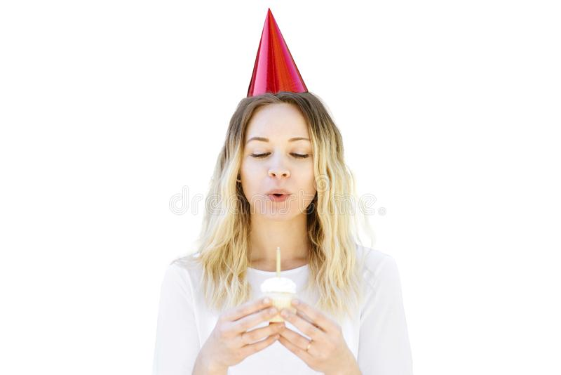 Blond Millennial Woman Blows Out Candle on Cupcake stock photos