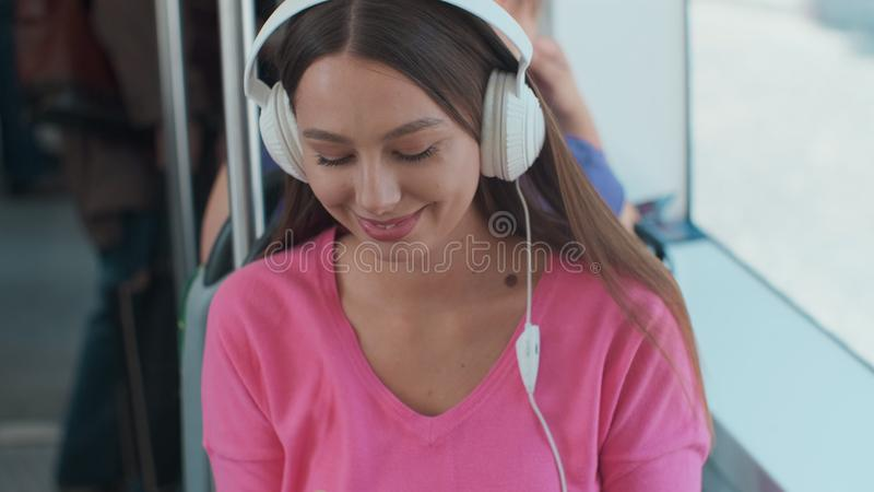 Young woman passenger enjoying trip at the public transport, sitting with headphones near the window in the modern tram. Young woman passenger enjoying trip at stock photography