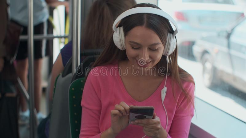 Young woman passenger enjoying trip at the public transport, sitting with headphones near the window in the modern tram. Young woman passenger enjoying trip at royalty free stock photography