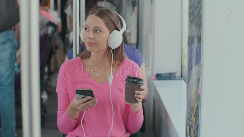 Young woman passenger enjoying trip at the public transport, sitting with headphones near the window in the modern tram. Young woman passenger enjoying trip at stock image