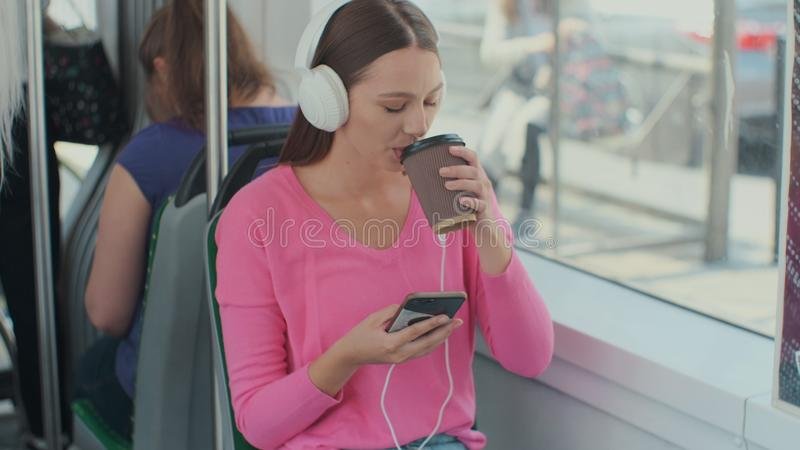 Young woman passenger enjoying trip at the public transport, sitting with headphones near the window in the modern tram. Young woman passenger enjoying trip at royalty free stock image