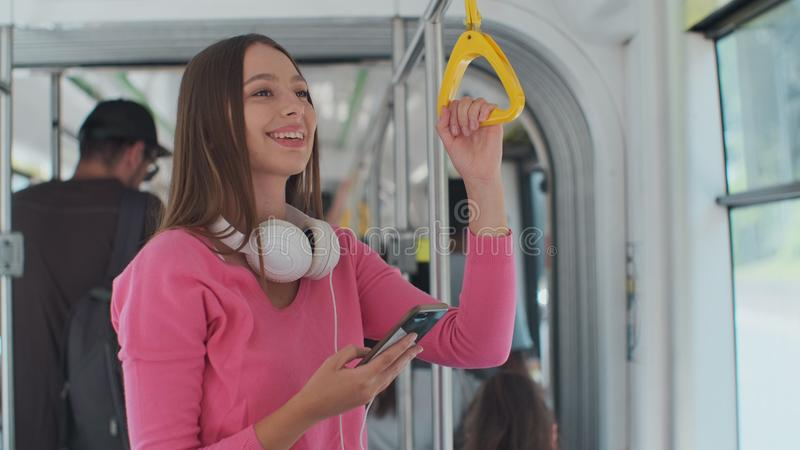 Young woman passenger enjoying trip at the public transport, standing with smartphone in the modern tram. Young woman passenger enjoying trip at the public royalty free stock images