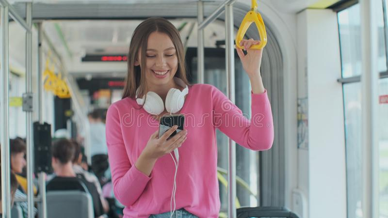 Young woman passenger enjoying trip at the public transport, standing with smartphone in the modern tram. Young woman passenger enjoying trip at the public stock photo