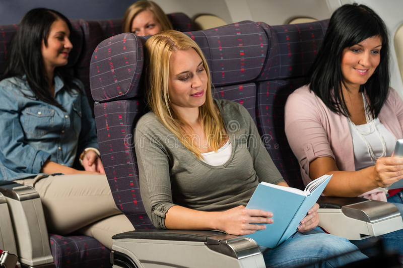 Young woman passenger read book airplane flight. Leisure travel young women passenger read book airplane cabin flight royalty free stock photography