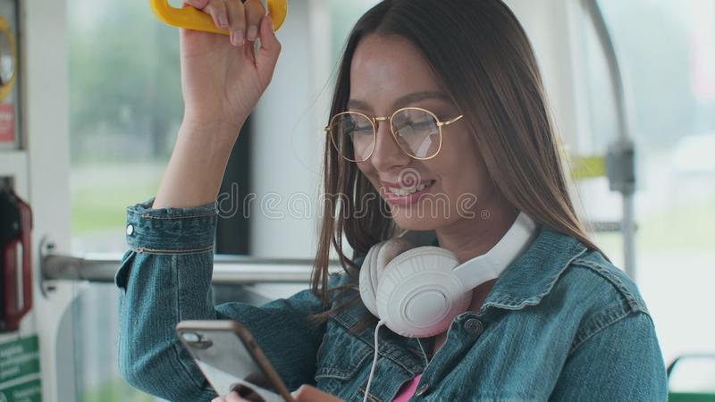 Young woman passenger standing with headphones and smartphone while moving in the modern tram, enjoying trip at the. Public transport stock image