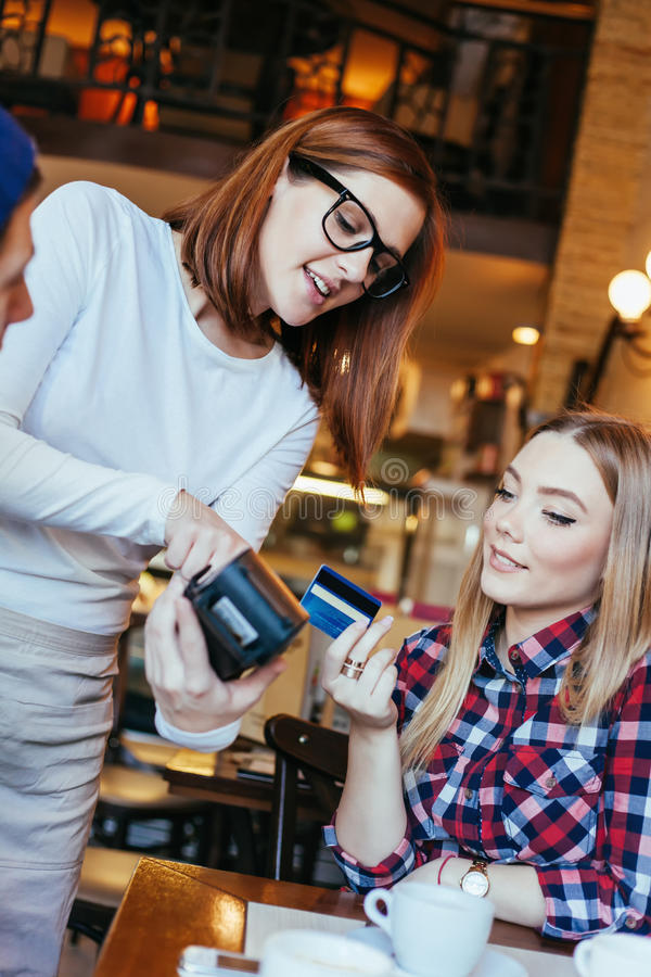 Young Woman Paying A Bill By Credit Card stock image
