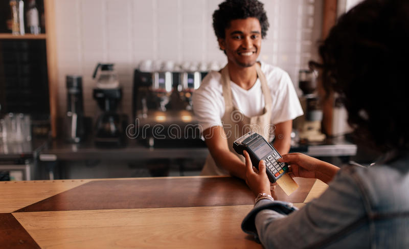 Young woman paying by credit card at cafe. Young women paying by credit card at cafe. Woman entering security pin in credit card reader with male barista stock photography