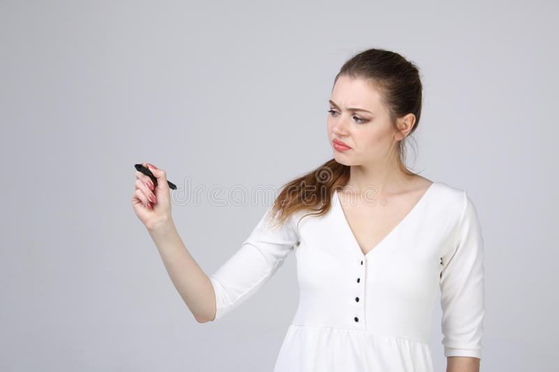 Young woman with pen on grey background stock photo