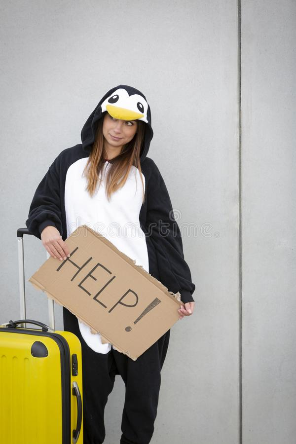 Young woman, with penguin costume and yellow suitcase, has to travel due to global warming. Symbolizes a sad penguin who has to leave his homeland because of royalty free stock image