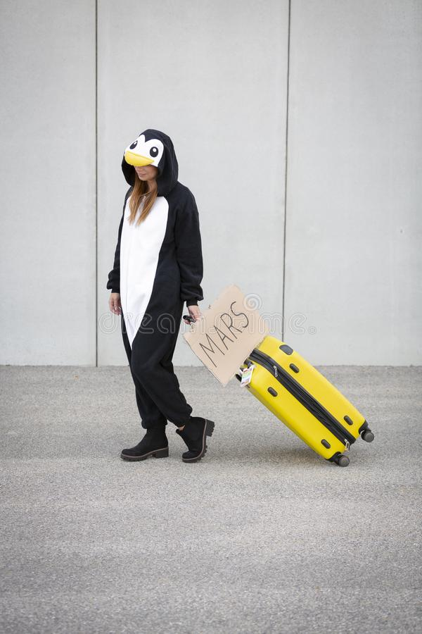 Young woman, with penguin costume and yellow suitcase, has to travel due to global warming. Symbolizes a sad penguin who has to leave his homeland because of royalty free stock photography