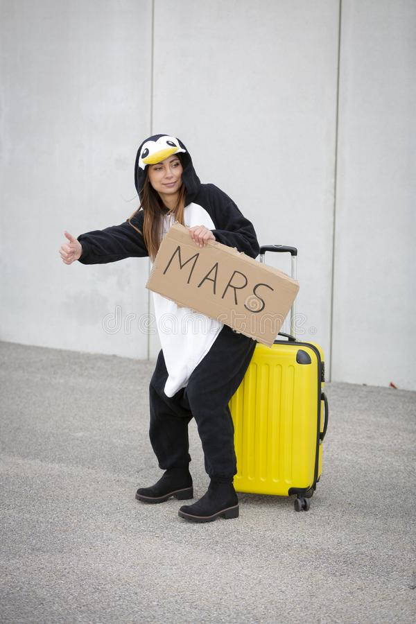 Young woman, with penguin costume and yellow suitcase, has to travel due to global warming. Symbolizes a sad penguin who has to leave his homeland because of stock photos