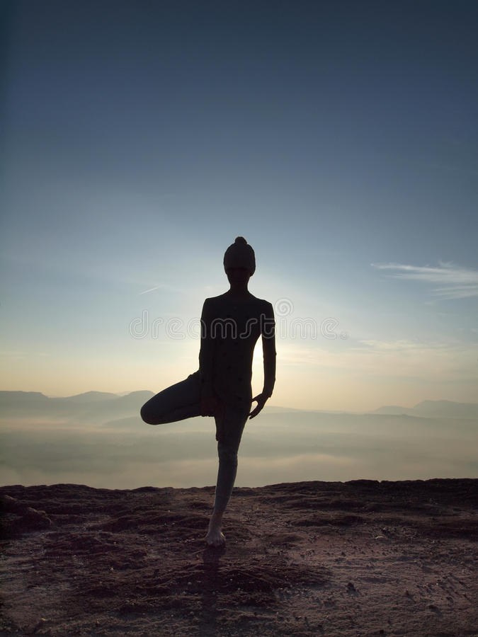 Young woman perform Yoga on the cliff in morning royalty free stock photo