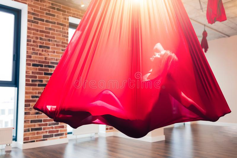 Young woman performig creative dance using red hammock as suspension equipment. Young woman performig creative dance using red hammock as a suspension equipment royalty free stock photo