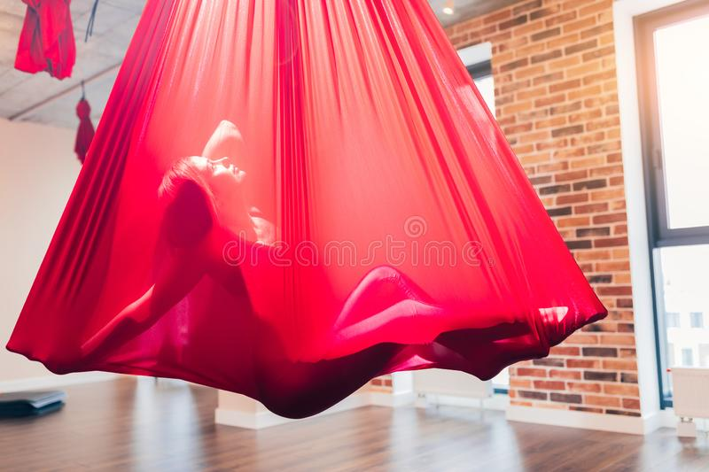Young woman performig creative dance using red hammock as suspension equipment. Young woman performig creative dance using red hammock as a suspension equipment royalty free stock photos