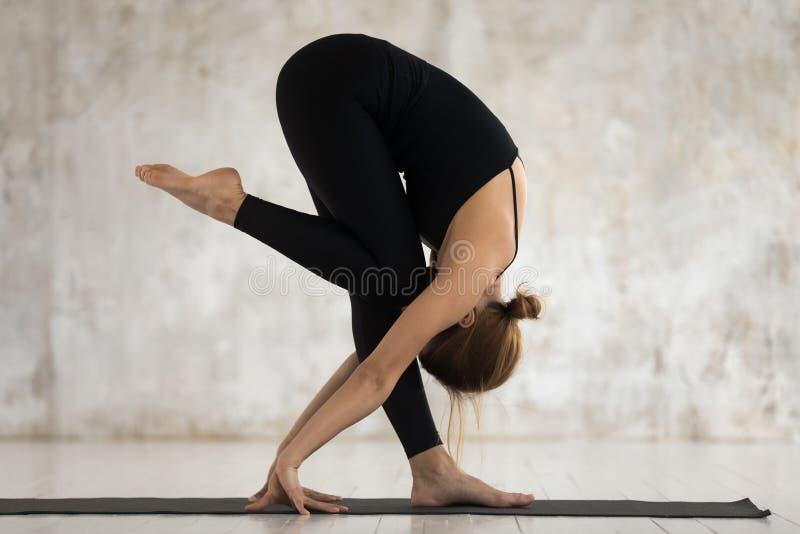 Young woman performing yoga asana Standing Forward Bend indoors. Woman performs yoga asana do Standing Forward Bend against beige textured studio grunge wall royalty free stock photos