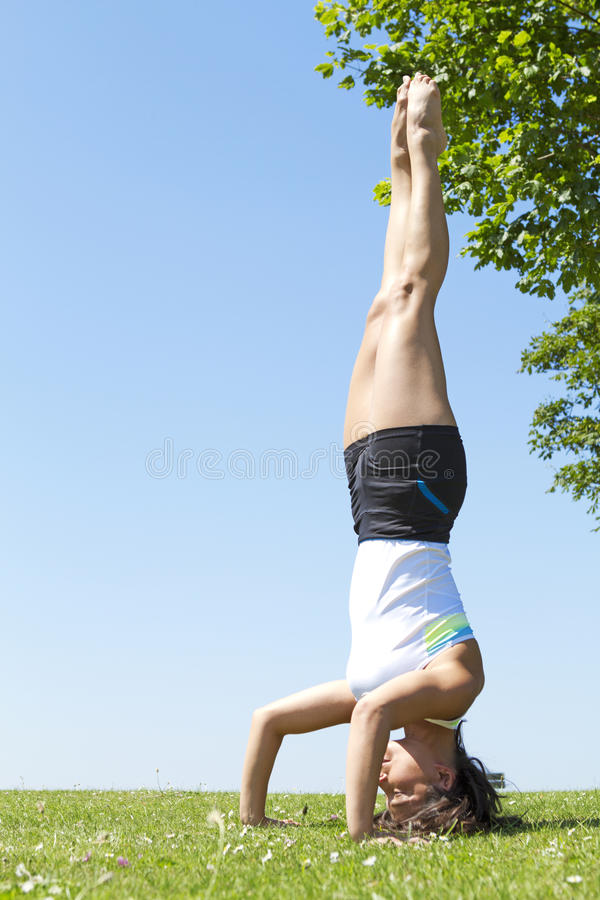 Young woman performing a yoga headstand stock photos