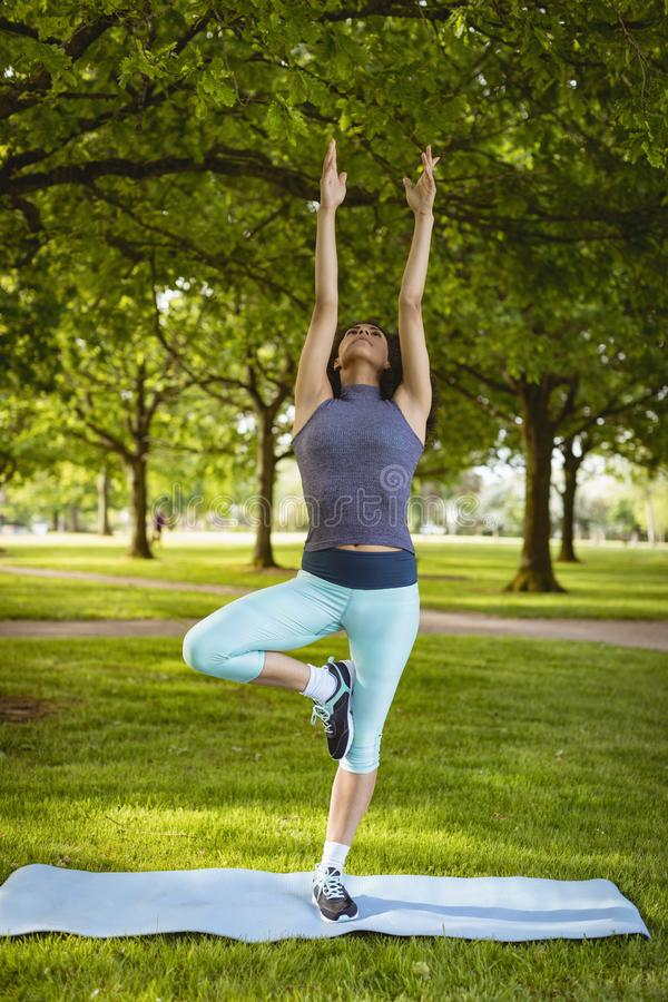 Woman performing yoga in the park royalty free stock images