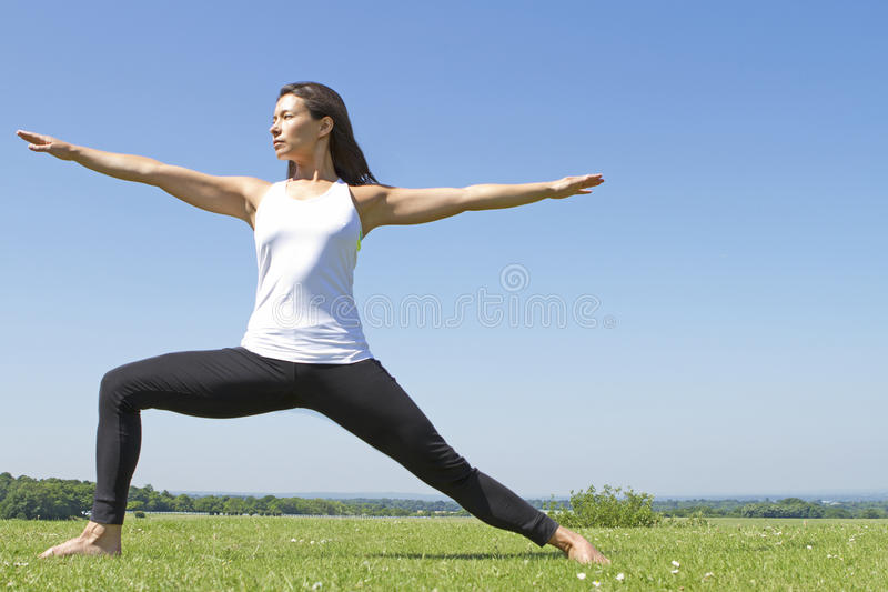 Young woman performing a yoga warrior pose stock photo